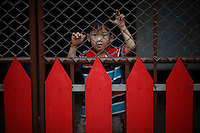 "A boy looks from behind a red fence in Sam Phrao, a village designated as ""Red Shirt Village of Democracy"" near Udon Thani in the northeastern Thailand June 27, 2011. The red shirts, supporters of ousted premier Thaksin Shinawatra, have been branding hundreds of villages as red to rally behind Thaksin's sister, Yingluck, who is leading the opposition ahead of July 3 general elections.   REUTERS/Damir Sagolj (THAILAND)"