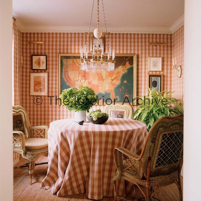 The dining room is decorated in brown and white gingham with a 1930s US map on one wall and is furnished with a set of late 19th century wicker armchairs