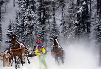 Group of horses and slide jockeys in masks and hardhats take corner towards the finish line