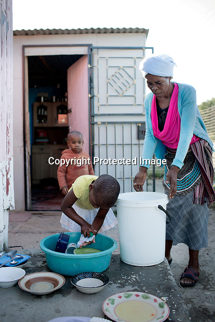 GUGULETU, SOUTH AFRICA - MARCH 12: A girl washes dishes with her grandmother outside their family home on December 12, 2014, In the Barcelona section of Guguletu, a township outside Cape Town, South Africa. Guguletu is one of the biggest black townships in Cape Town (Photo by Per-Anders Pettersson)