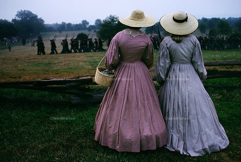 Women in period clothing watch soldiers Manassas National Park during a reenactment of a Civil War battle.