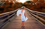 Angel Girl Barefoot on Wood Pier with Autumn Trees in background, at dusk, short white dress blowing in wind.