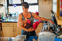 A mother breastfeeds her baby while preparing  a meal at her stove in the ktichen.<br /> <br /> 30 August 2012<br /> Hampshire, England, UK