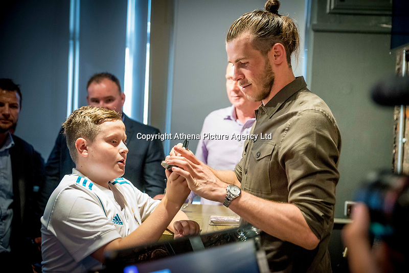 "Pictured: Gareth Bale meets a young fan at his Elevens Bar in Cardiff, Wales, UK. Thursday 12 July 2018<br /> Re: Last night (Thurday 12 July) Elevens Bar & Grill and the Football Association of Wales jointly hosted a Q&A evening with Gareth Bale. At the event, Gareth unveiled a new piece of memorabilia for Elevens – his match worn boots from this year's Champions League Final with which he scored that incredible overhead kick.<br /> The event, hosted at Elevens Bar & Grill was open to members of the public with doors opening at 6pm on Thursday evening. People started queueing from 3pm, with a cross-section of fans of all ages in Wales shirts and bucket hats. <br /> The Q&A, conducted by Ian Gwyn Hughes from the FAW, discussed all aspects of his career so far, from growing up in Cardiff to winning 4 Champions League medals with Real Madrid. On growing up in Whitchurch, Gareth said: ""My family were a huge influence on me growing up. My parents were so supportive, taking me here there and everywhere so I could play football. Growing up I can hardly remember not being with a football – I even took one to bed!""<br /> There were a lot of youngsters in the audience, eager to hear from their hero. Gareth's advice to them? ""Work hard for what you want and who knows where that could take you.""<br /> As a left-footer, Ryan Giggs,  Wales' national team manager was someone he looked up to growing up. Gareth mentioned it was great to beat Ian Rush's goal scoring record for Wales with his childhood idol as manager. ""I knew I'd levelled his record at half time, I needed one more to break it. The manager wanted to take me off but I said give me another 15 minutes to see if I can do it. Luckily on 61 minutes our goalkeeping coach took too long to do the substitution on the paper, so it gave me an extra minute. It worked out perfectly."""