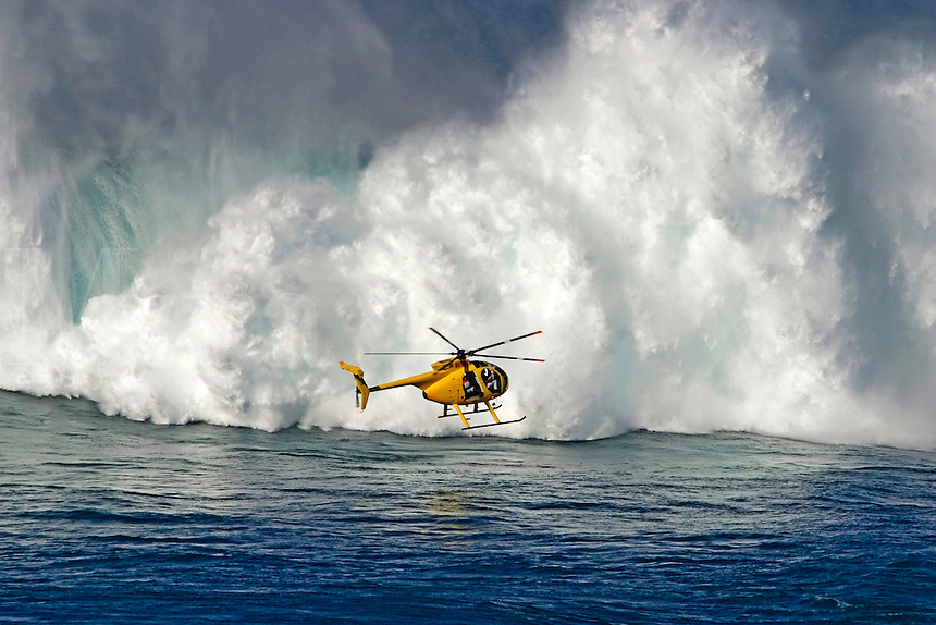 A helicopter hovers in front of 60 foot surf crashing on Maui's Northshore at Peahi (Jaws).