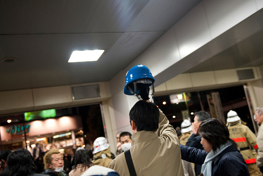 A man holding an earthquake protection hard hat, Shinagawa station, Tokyo, 11 March 2011. After a huge earthquake in north-east Japan several million people in Tokyo struggle to return home.