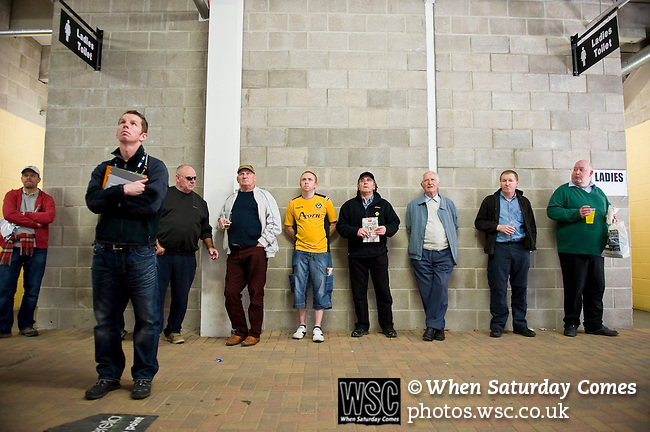 Newport County 1 Exeter City 1, 16/03/2014. Rodney Parade, League Two. Newport County finally return to the Football league after years of turmoil but a poor run of results has dented hopes of reaching the play-offs while Exeter City battle relegation. Half time at Rodney Parade fans watch the scores coming in from around the country. Photo by Simon Gill