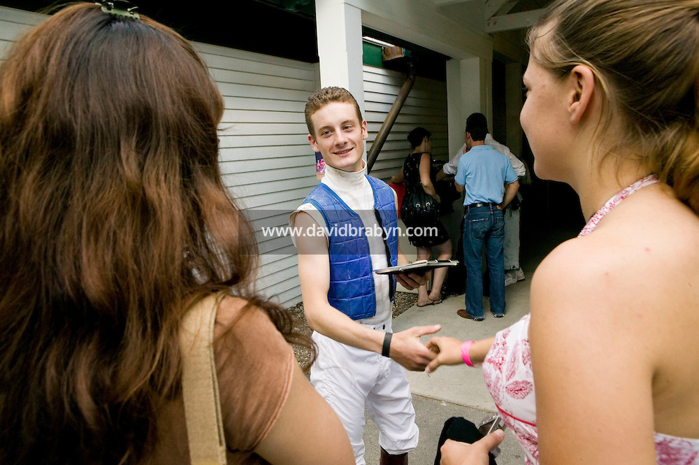 Jockey Julien Leparoux (C) shakes hands with two young women that came up to introduce themselves after a race in Saratoga Springs, NY, United States, 4 August 2006. The women then asked him if he would pose with them for a photograph.