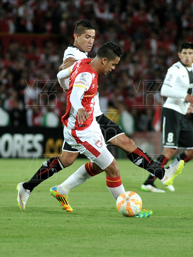 BOGOTA- COLOMBIA – 26-02-2015: Yulian Anchico (Der.) jugador del Independiente Santa Fe de Colombia, disputa el balón con Felipe Flores (Izq.) jugador de Colo Colo de Chile, durante partido entre Independiente Santa Fe de Colombia y Colo Colo de Chile, por la segunda fase, grupo 1, de la Copa Bridgestone Libertadores en el estadio Nemesio Camacho El Campin, de la ciudad de Bogota. / Yulian Anchico (R) player of Independiente Santa Fe of Colombia, figths for the ball with Felipe Flores (L) player of Colo Colo of Chile during a match between Independiente Santa Fe of Colombia and Colo Colo of Chile for the second phase, group 1, of the Copa Bridgestone Libertadores in the Nemesio Camacho El Campin in Bogota city. Photo: VizzorImage / Luis Ramirez / Staff.