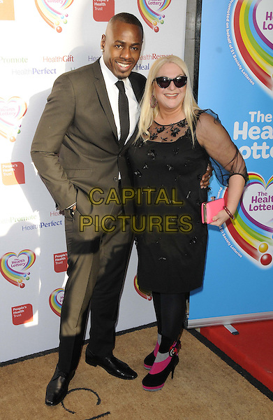 Ben Ofoedu & Vanessa Feltz.The Health Lottery Fundraising reception at Claridge's Hotel, London, England..28th March 2013.full length brown suit black dress sheer pink clutch bag sunglasses shades couple .CAP/CAN.©Can Nguyen/Capital Pictures.