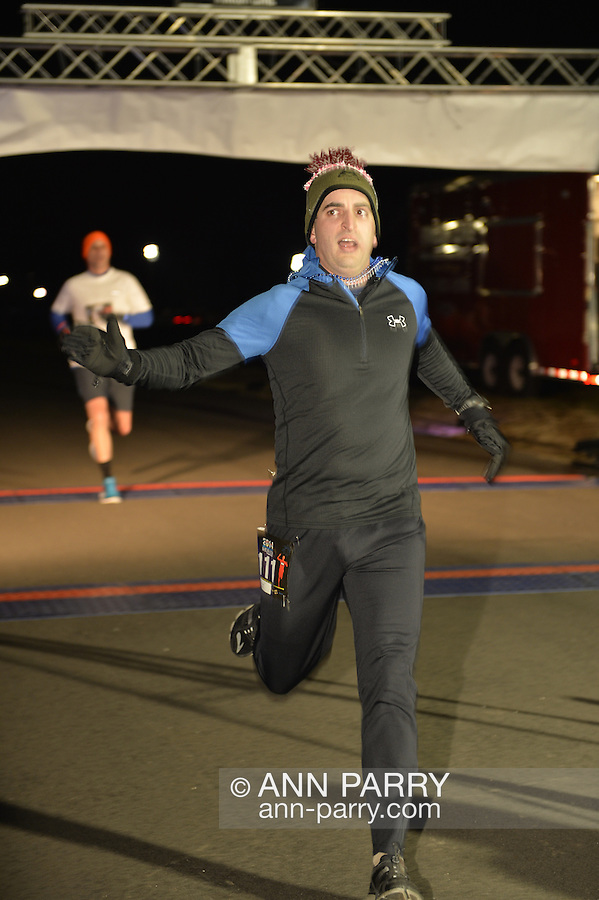 East Meadow, New York, USA. January 1, 2015. A runner crosses the finish line in the 5K New Year's Eve DASH to support the Long Island Council on Alcoholism and Drug Dependence (LICADD) at the Twin RInks Ice Center at Eisenhower Park in Long Island. A Skatin' New Year's Eve event started hours earlier and a New Year's Eve Party, open to runners, family and friends continued until 2:30 a.m.