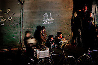 Three children wait for their mother to return from the breadline at a bakery in the Shaar neighborhood of Aleppo. 12:15AM - December 07, 2012.<br />