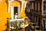 An afro-latino man peers from the balcony of a colonial heritage building in the Ciudad Vieja or old town of Cartagena, Colombia.  The city is a UNESCO world heritage site.
