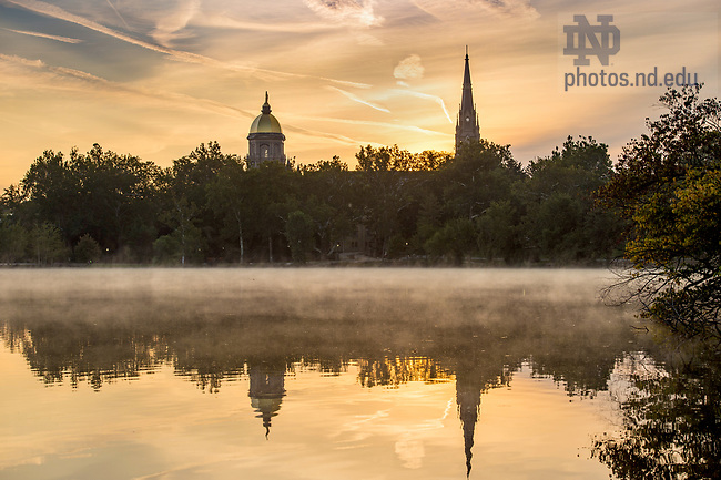 September 12, 2017; View of sunrise from St. Mary's Lake of the Golden Dome and the steeple of the Basilica of the Sacred Heart.  (Photo by Barbara Johnston/University of Notre Dame)