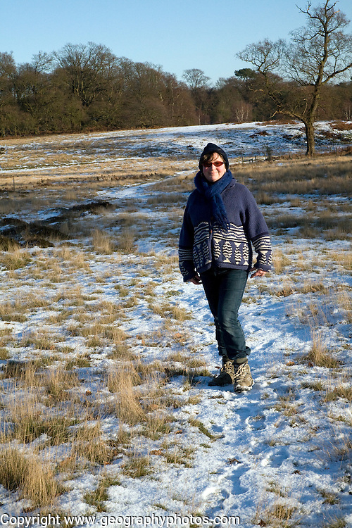Front view of model released mature woman standing in heathland with covering of snow, Suffolk, England, UK