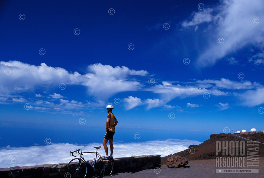 A biker rests atop Haleakala in Haleakala National Park at a 10,023-ft. elevation, while looking out over the Pacific Ocean and at clouds. Science City observatories are in the distance.