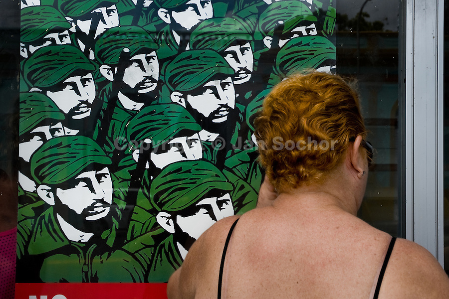 A Cuban woman look through a shop window covered by the Fidel Castro's propaganda poster, checking out if a desired product is available, Santiago de Cuba, Cuba, 29 July 2008. About 50 years after the national rebellion, led by Fidel Castro, and adopting the communist ideology shortly after the victory, the Caribbean island of Cuba is the only country in Americas having the communist political system. Although the Cuban state-controlled economy has never been developed enough to allow Cubans living in social conditions similar to the US or to Europe, mostly middle-age and older Cubans still support the Castro Brothers' regime and the idea of the Cuban Revolution. Since the 1990s Cuba struggles with chronic economic crisis and mainly young Cubans call for the economic changes.
