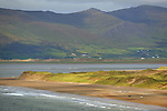 Horses and riders round the bend at the far end of the track on Rossbeigh Strand in County Kerry.