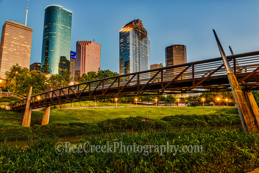 Houston Bagby to Sabine promenade bridge in downtown with the skyline in the background. Houston bagby to sabine bridge in downtown with the skyline in the background at blue hour. This pedestrian bridge for the bagby and sabine promenade is a great way to get around on the hike and bike trails as it crosses the Buffalo Bayou so you can cross over into the city without getting onto the busy streets.