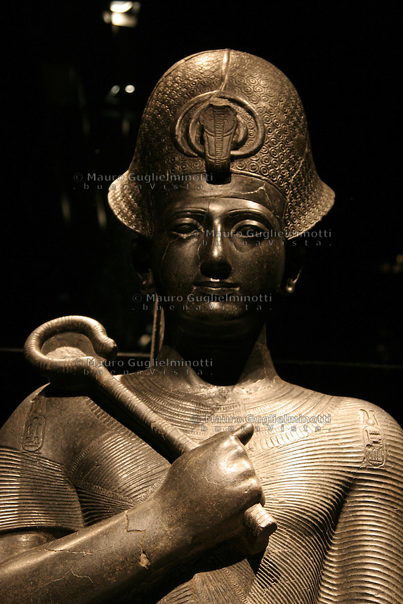 ITALIA - Torino - Museo Egizio  Il faraone Ramesse II..Diorite XIX dinastia regno di Ramesse II (1279 - 1213 a.C.) tempio di Amon Tebe..Il trono è decorato dai simboli dell'Unione (sema) e delle due Terre rappresentati dal papiro (Basso Egitto) e dal loto (Alto Egitto) Il re porta la corona azzurra khepresh e lo scettro heka  La scena alla base con prigionieri Nubiani e Siriani mostra la potenza del faraone Ai suoi piedi scolpite le figure della moglie Nefertari e del figlio