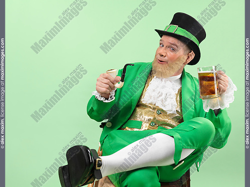 Cheerful Leprechaun in bright green clothes holding a smoking pipe and a beer