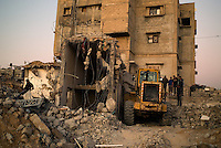 Al Tufa'ah, Gaza Strip, 19 Nov 2009.Almost a year after the 'Cast Lead' israeli operation, inhabitants are still cleaning up the rubles of their homes, trying to recycle all possible material as Gaza is still under complete blockade from Israel. Hundreds of houses, farms and factories had been destroyed and bulldozed over by the Israeli army, flattening approximately an area 10km square, ruining countless families, left resourceless in what amounts to collective punishment..