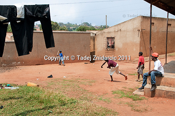 Felix Barugahare, 11 (blue T-shirt), and Augustus Owinyi, 12 play baseball while Jonathan Kizza (red T-shirt), 11, and Ivan Matovu, 13 watch in Nsambya, neighbourhood of Kampala, Uganda on July 28 2011. Felix Barugahare plays 2nd base and is the youngest player on Rev. John Foundation Little League baseball team. Augustus Owinyi plays 1st base, Jonathan Kizza plays 2nd base and Ivan Mutovu is starting pitcher. Young players often play close to their homes outside of the regular daily practice.