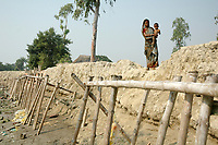 A Bengali woman with her baby stands on an elivated bank of a river in Sunderbans, West Bengal, India