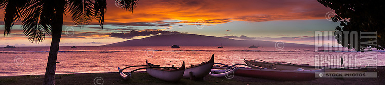 A man strolls the shoreline near outrigger canoes on a Maui beach as the sun sets behind Lana'i.