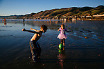 Ruthawna Collins (right), 4, of Forsyth, Missouri, plays along the shore of Pismo Beach, California with her brother Micah, 8, December 22, 2014. The trip was her first trip to the beach.