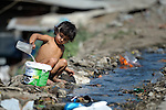 "THIS PHOTO IS AVAILABLE AS A PRINT OR FOR PERSONAL USE. CLICK ON ""ADD TO CART"" TO SEE PRICING OPTIONS.   A Roma girl collects drinking water from a dirty stream flowing through the Maxsuda neighborhood of Varna, Bulgaria."