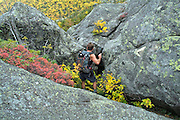 Hiking on the Subway Trail during the early months of autumn-.The Subway Trail is a side trail off the King Ravine Trail, which travels through a large boulder field in King Ravine. Located in the White Mountains, New Hampshire USA. ..Notes: The subway reconnects with the King Ravine Trail..Snow can be found in the ice caves of this ravine during the summer months
