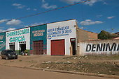 Pará State, Brazil. São Félix do Xingu. Evangelical church in a row of shops with a clothes shop, a restaurant and a car repair shop.