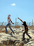 A Palestinian and foreign protesters clash with Israeli soldiers during a demonstration against Israel's controversial separation barrier in the West Bank village of Bilin near Ramallah on July3,2009. Photo by Issam Rimawi
