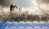 30 JUN 2011 - LONDON, GBR - Competitors dive into the water at the start of the second men's supersprint elimination wave at the GE Canary Wharf Triathlon (PHOTO (C) NIGEL FARROW)