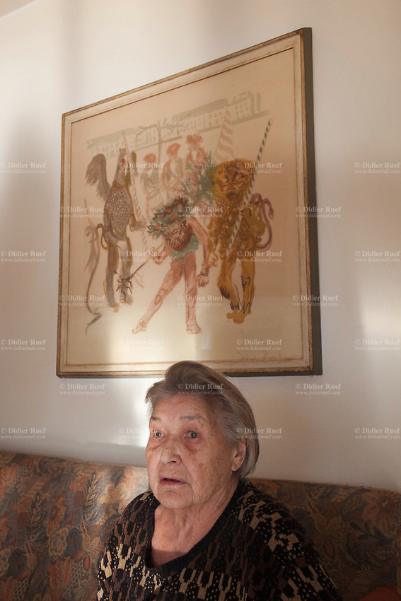 Switzerland. Canton Ticino. Sala. Elsy (Elsa) Hofer Ferrari Ramuz is 86 years old. She seats on a sofa in her living room. On the wall, a painting by the artist Irène Zurkinden on the Basel Carnival. Elsy Hofer Ferrari Ramuz is the niece of Charles-Ferdinand Ramuz (September 24, 1878 – May 23, 1947) who was a French-speaking Swiss writer.  14.11.2017 © 2017 Didier Ruef