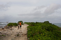 A Marshall Islander walks his bicycle on the narrow road that forms a causeway between Jaluit Atoll's main town of Jabor and the local airstrip.