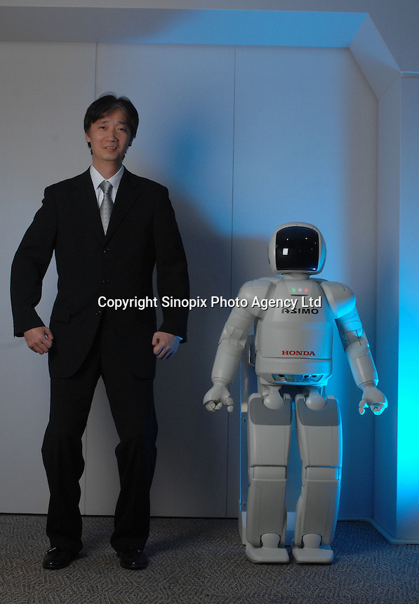 "The Asimo robot built by Honda with it's developer and chief engineer Masato Hirose at the Honda headquarters in Tokyo where it lives in the office and performs simple tasks. Asimo is one of the most advanced humanoids in the world and is being developed as a ""home"" help robot."