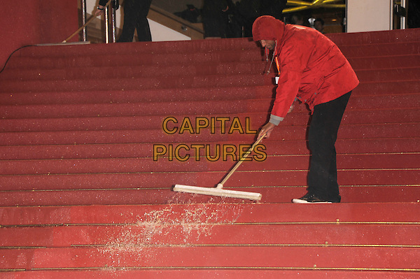 Clearing the rainwater from the red carpet.'Jagten' screening at the 65th  Cannes Film Festival, France 20th May 2012.gv general view full length cleaner red jacket black trousers broom wet stairs steps .CAP/PL.©Phil Loftus/Capital Pictures.