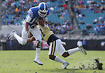 Quarterback Stephen Johnson #15 of the Kentucky Wildcats breaks a tackle by defensive back Lance Austin #17 of the Georgia Tech Yellow Jackets during the first half of the TaxSlayer Bowl at EverBank Field on Saturday, December 31, 2016 in Jacksonville, Florida. Photo by Michael Reaves | Staff.