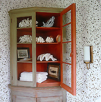 Inside an antique painted corner cupboard Tom Scheerer has arranged resin coral and shells with beach towels and whaling prints