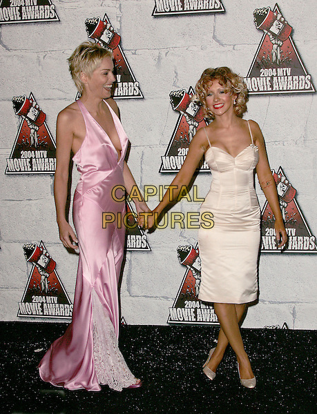 SHARON STONE & CHRISTINA AGUILERA.Attends the 2004 Mtv Movie Awards held at The Sony Picture Studios in Culver City, California  .June 6, 2004.full length, full-length, white, silk, satin dress, pink, plunging neckline, holding hands.www.capitalpictures.com.sales@capitalpictures.com.©Capital Pictures