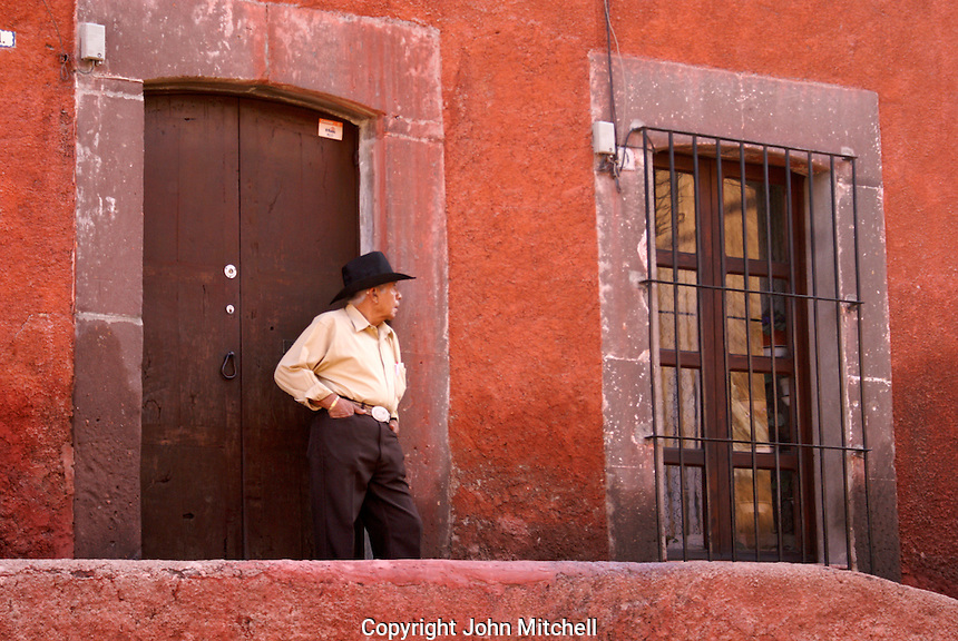 Mexican man standing in the doorway of a Spanish colonial building  in San Miguel de Allende, Mexico