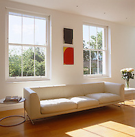 A leather sofa by Jasper Morrison for Cappellini stands in front of a pair of sash windows in this light-filled living room