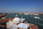 Venice and the busy waterways, showing assorted craft, and many famous landmarks. Foreground the dome and courtyard of San Giorgio Maggiore. Venice, Italy.