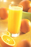 glass of orange juice with cut oranges