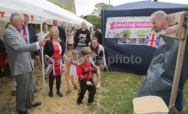 12 June 2016 - Prince Charles, Prince of Wales reacts as 7 year old Quinlan Shepherd (C) hurls a sponge at a man in the stocks at a street party in Brimpsfield, Gloucestershire, as part of the three day celebrations for Queen Elizabeth II's official 90th birthday. The Big Lunch is an annual event started by the Eden Project which aims to get as many people as possible to have lunch together, in their neighbourhoods, in order to encourage more of a community spirit throughout the Nation. Photo Credit: ALPR/AdMedia