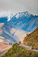 Snow covered Alaska Range mountains are a background as tourist buses travel the gravel road of Denali National Park through Polychrome Pass