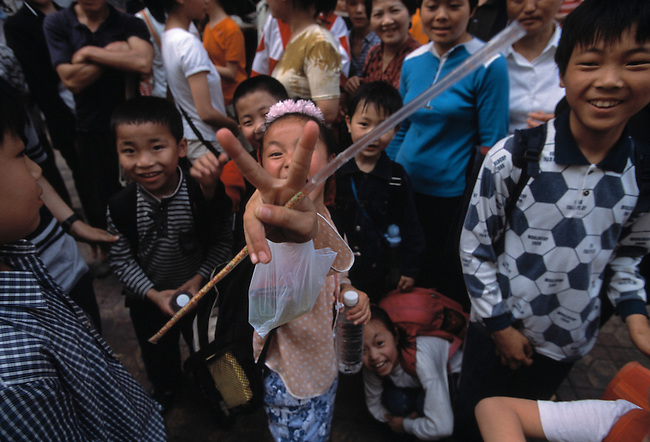 Children on street in Fuling, China, Asia; mug for camera; youth; faces; victory; peace sign; hot afternoon; city of Fuling; 041703