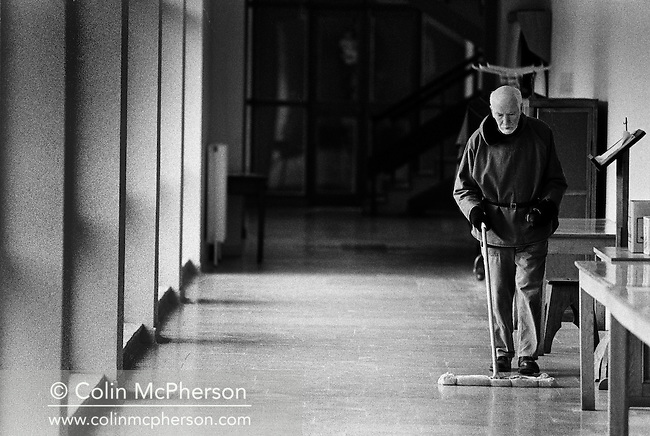 A monk cleaning the floor in a corridor at Sancta Maria Abbey at Nunraw, East Lothian, home since 1946 to the Order of Cistercians of the Strict Observance. Around 15 monks were resident at Nunraw in 1996, undertaking a mixture of daily tasks and strict religious observance. The present purpose-built building dates from 1969 when the monks moved from the nearby Nunraw house.